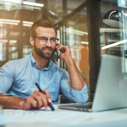 Customer support. Portrait of young and cheerful businessman in eyeglasses and formal wear talking on the phone and smiling while sitting in the office. Working place. Business concept